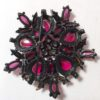 Black brooch purple and red stones