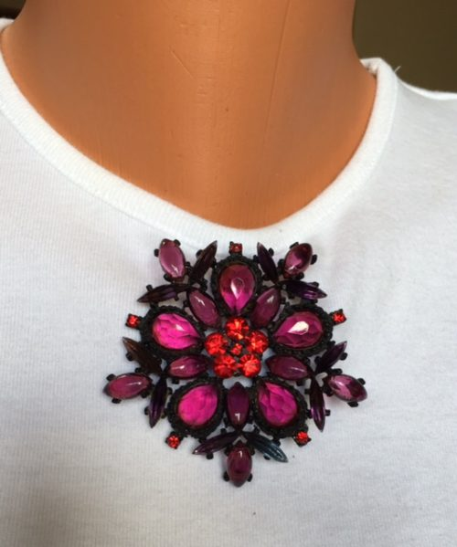 Black brooch purple stones with red center