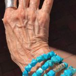turquoise wrap bracelet on my hand and silver ring