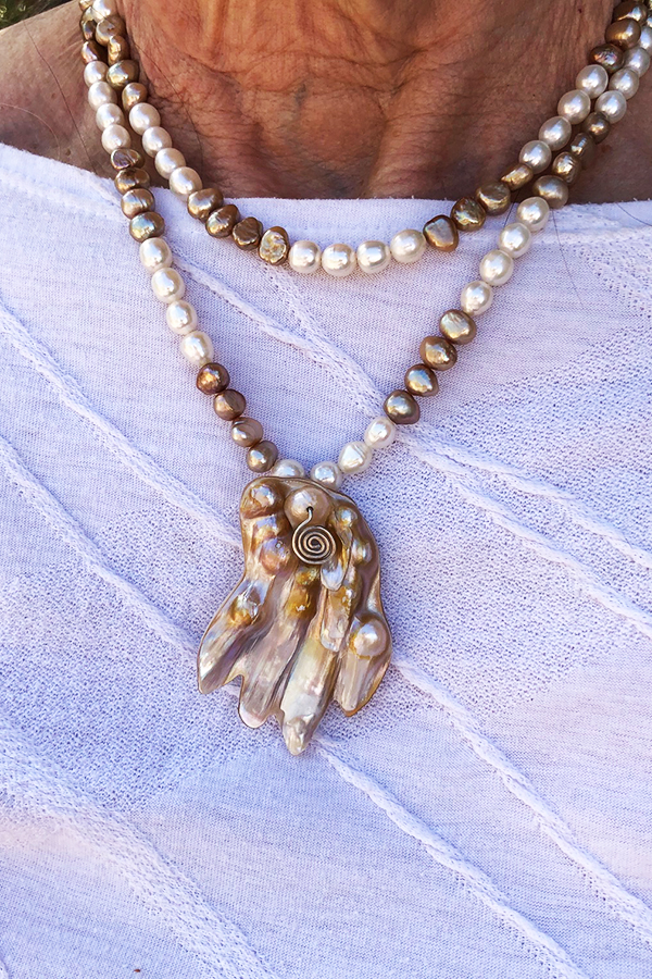 Two strand pearl necklace with hand pendant