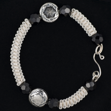 coiled silver bracelet with disc beads