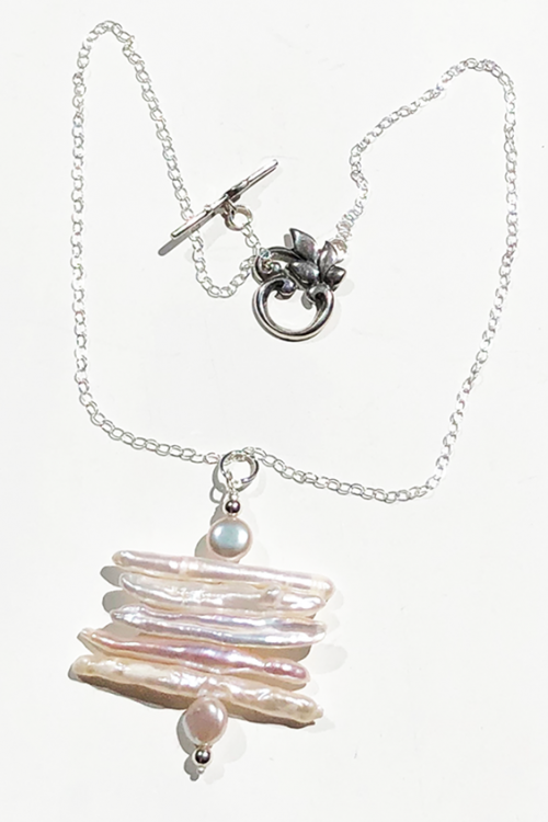 Long white pearl pendant on silver chain